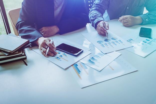 Hombres y colegas de negocios asiáticos de mediana edad analizando gráficos de negocios.