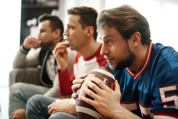 Hombres concentrados viendo el partido de fútbol en casa