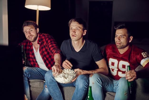 Hombres concentrados viendo el partido de futbolín en la noche