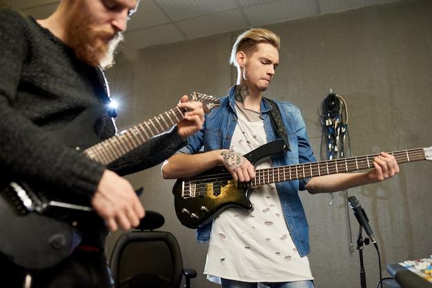 Hombres creativos tocando guitarras en estudio