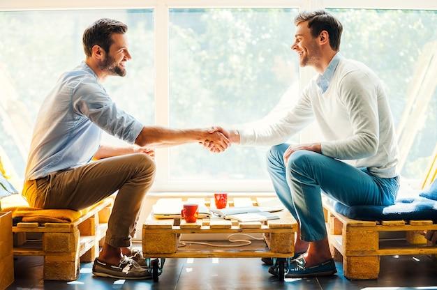 Hombres dándose la mano. vista lateral de dos hombres jóvenes felices dándose la mano mientras está sentado frente a la ventana