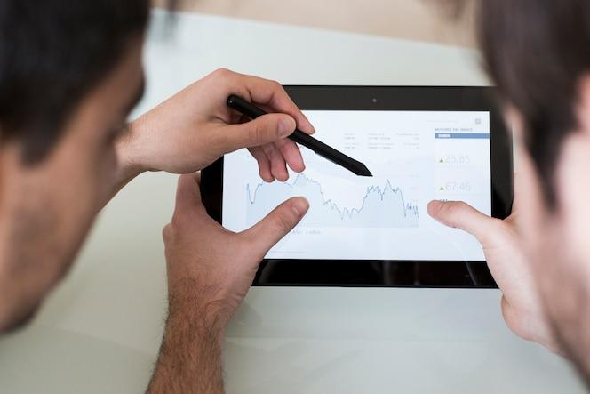 Hombres de cultivos discutiendo gráfico en tableta