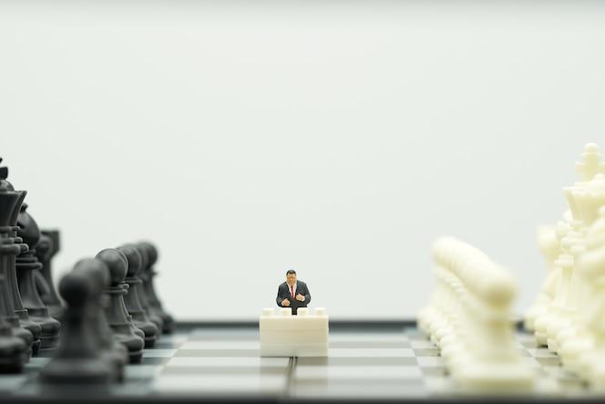Hombres de negocios de la gente en miniatura que se colocan en un tablero de ajedrez con un ajedrez