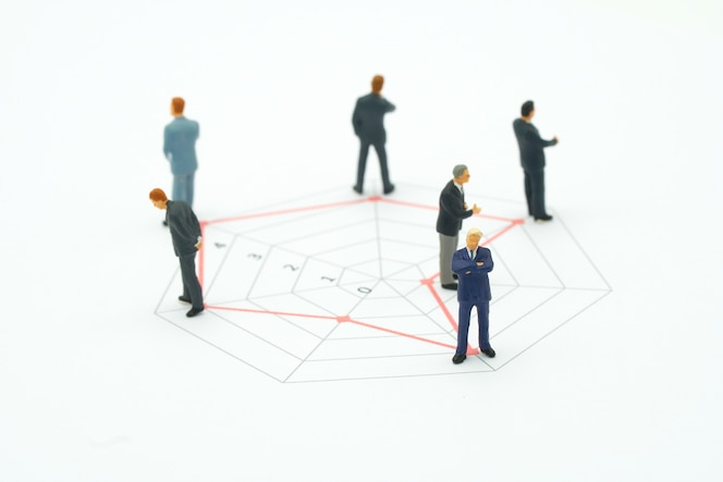 Hombres de negocios de la gente miniatura que se colocan en gráficos de un círculo de la habilidad diversa