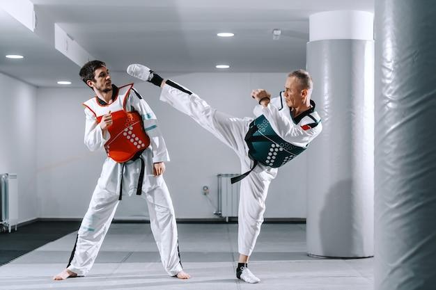 Hombres deportivos entrenando en accesorios de tekwondo.