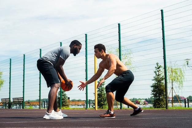 Hombres deportivos jugando baloncesto urbano bajo ángulo de tiro