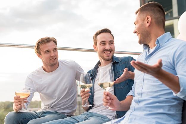 Hombres dialogando en una fiesta.