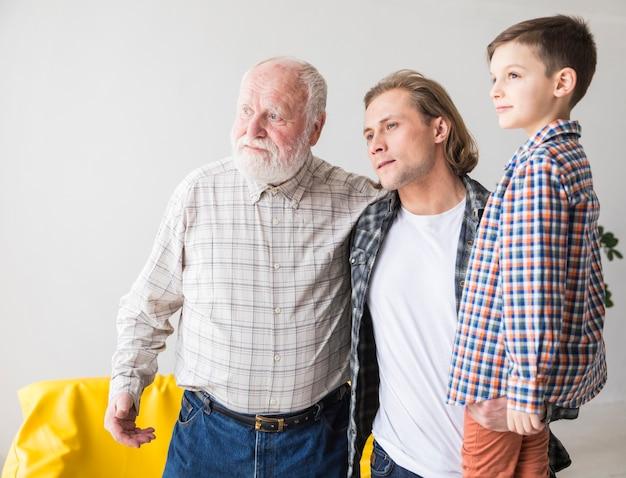 Hombres de diferentes generaciones de pie y mirando a otro lado.