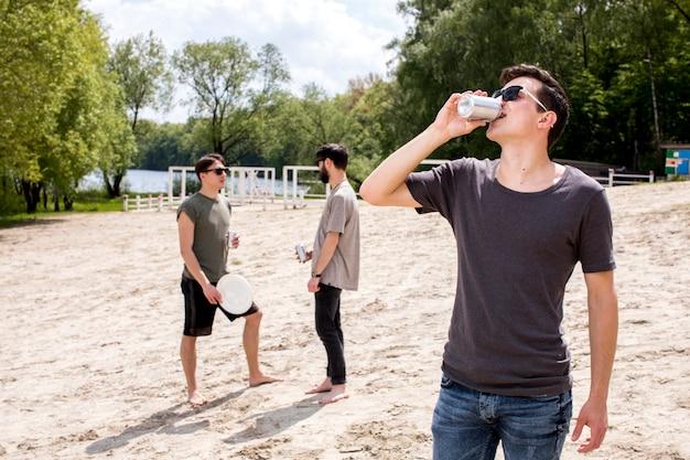 Hombres disfrutando de bebidas y sosteniendo frisbee.