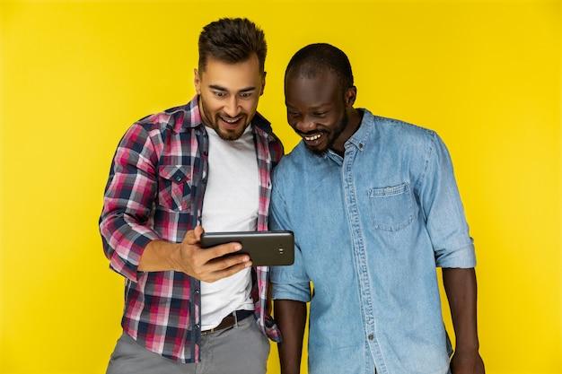 Hombres disfrutando de ver un video en una tableta