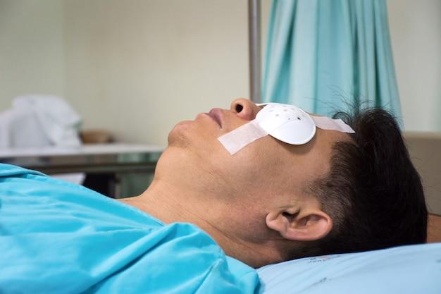 Los hombres duermen y usan protección para los ojos después de una cirugía ocular en la habitación del hospital.