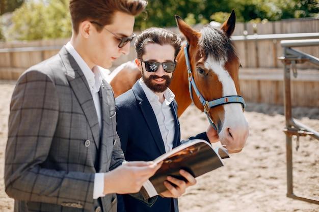 Hombres elegantes de pie junto al caballo en un rancho