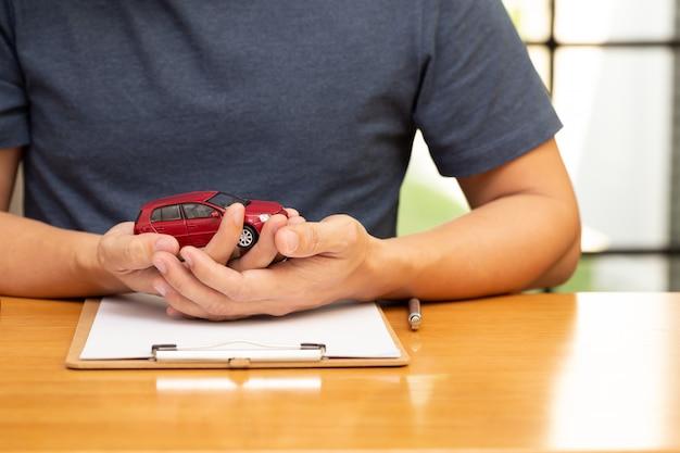 Los hombres eligen comprar y firmar pólizas de contratos con seguros de vehículos y automóviles.