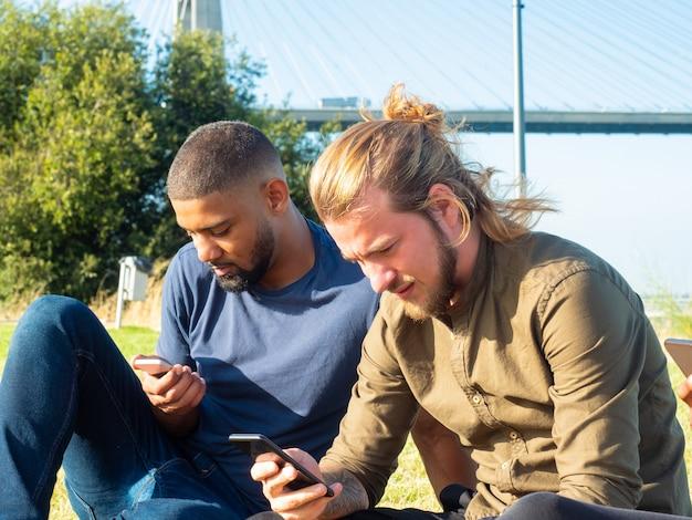 Hombres enfocados usando teléfonos inteligentes al aire libre