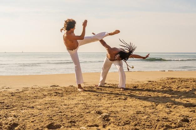 Los hombres entrenan a la capoeira en la playa: concepto sobre personas, estilo de vida y deporte. entrenamiento de dos luchadores