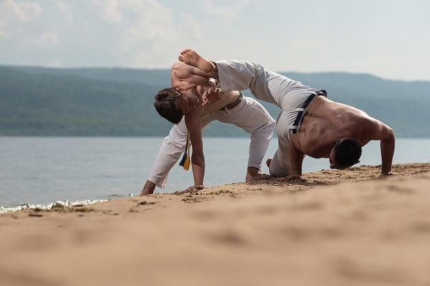 Los hombres entrenan a la capoeira en la playa: concepto sobre personas, estilo de vida y deporte.