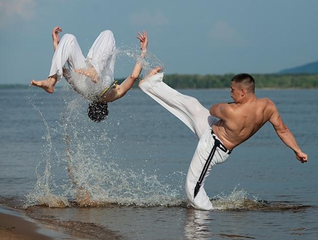 Hombres entrenan a capoeira en la playa - concepto sobre personas, estilo de vida y deporte.