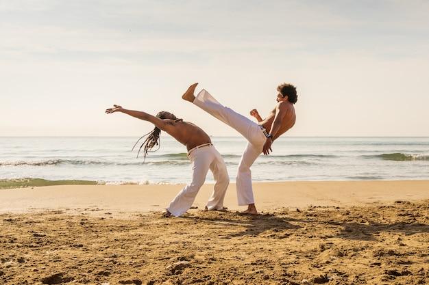 Hombres entrenando capoeira en la playa