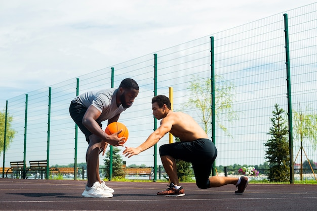 Hombres estadounidenses jugando baloncesto urbano tiro largo