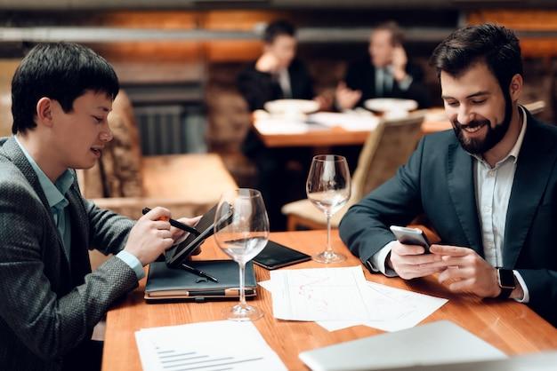 Los hombres están mirando sus teléfonos.