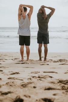 Hombres, estirar, en la playa