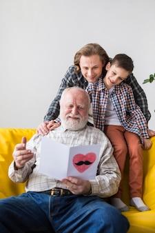Hombres de familia de diferentes generaciones viendo tarjeta de regalo.