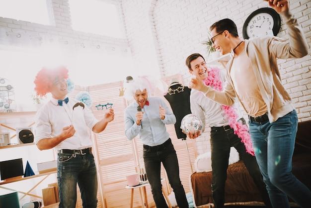 Hombres felices con pajaritas cantando canciones de karaoke en la fiesta.