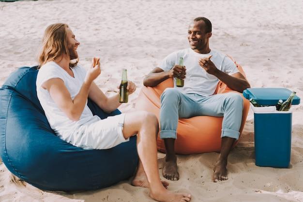 Los hombres felices tienen bocadillos y cerveza en la orilla