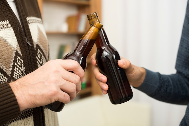 Hombres golpeando botellas de alcohol en la habitación