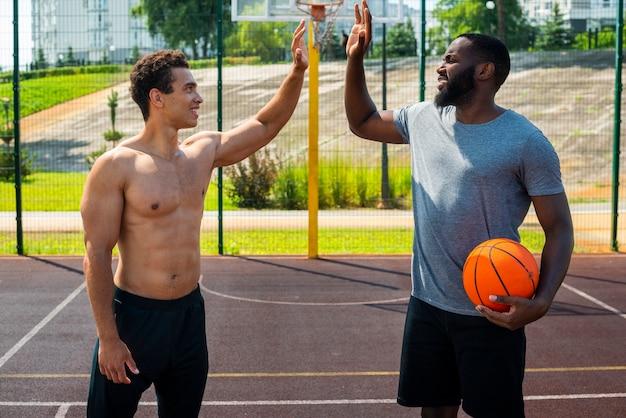 Hombres guapos jugando baloncesto urbano tiro medio