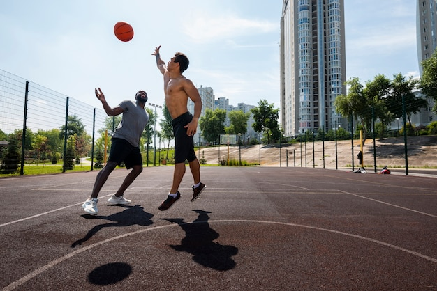 Hombres guapos lanzando pelota de baloncesto