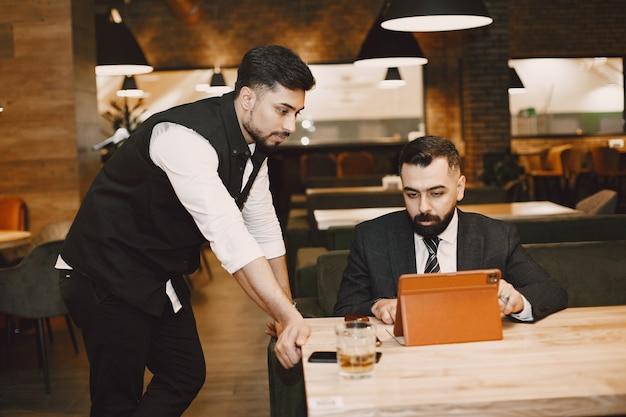 Hombres guapos en trajes negros, trabajando en un café
