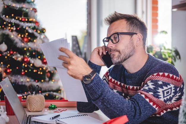 Hombres hablando por teléfono y sosteniendo facturas