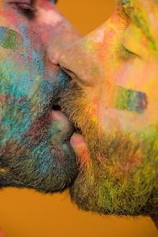 Hombres homosexuales pintados artísticamente besándose apasionadamente.