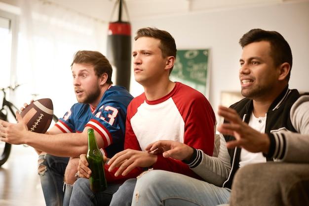 Hombres infelices mientras ve fútbol americano