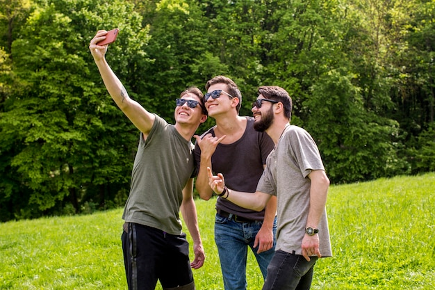 Hombres jovenes alegres que toman el selfie en naturaleza