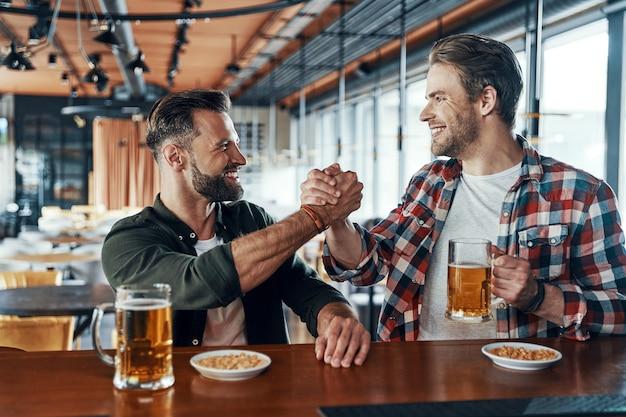 Hombres jóvenes alegres en ropa casual dándose la mano y bebiendo cerveza mientras pasan tiempo en el pub