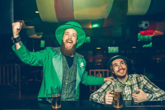 Hombres jóvenes alegres se sientan en barra de bar en pub y animando. ellos miran hacia adelante. los chicos tienen jarras de cerveza en la barra de bar. joven a la izquierda usar traje verde.