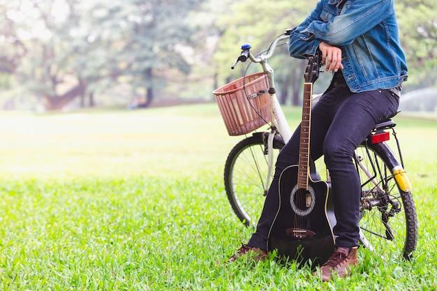 Los hombres jovenes asiáticos del retrato que se sientan en la bicicleta tocan la guitarra