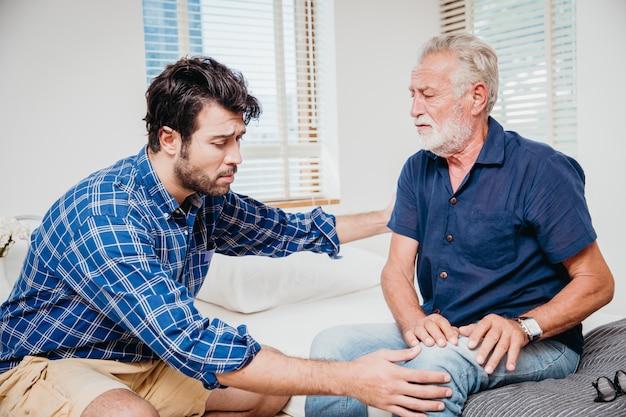 Los hombres jóvenes de atención médica tío anciano en el hogar, el dolor de anciano en la pierna de la rodilla.