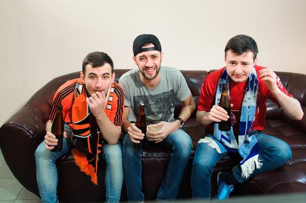 Los hombres jóvenes beben cerveza, comen papas fritas y apuestan por el fútbol