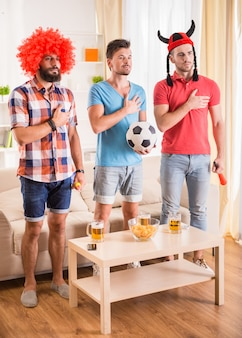 Los hombres jóvenes beben cerveza, comen pizza y animan al fútbol