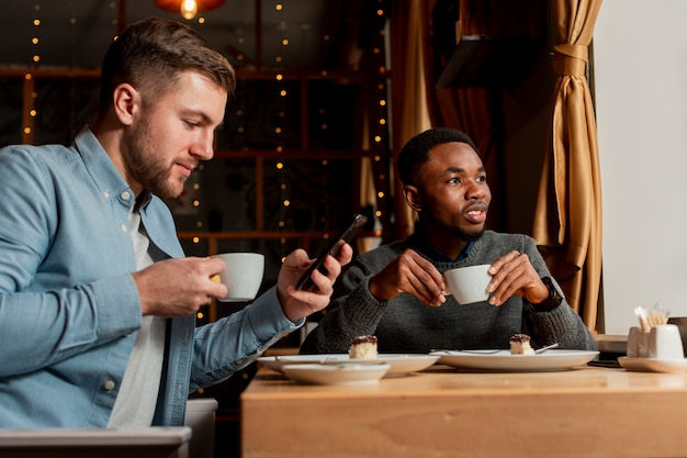 Hombres jóvenes bebiendo café juntos