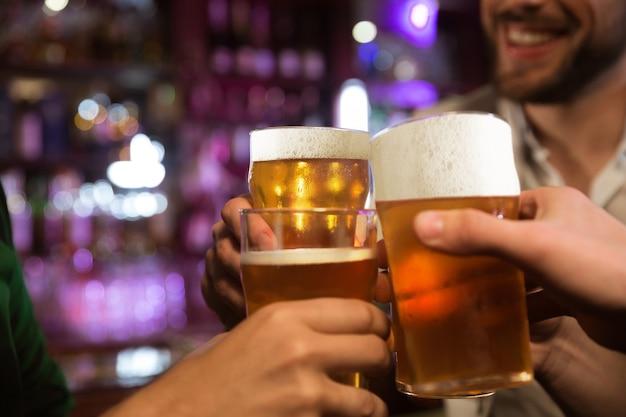 Hombres jóvenes brindando con cerveza mientras están sentados juntos en un pub