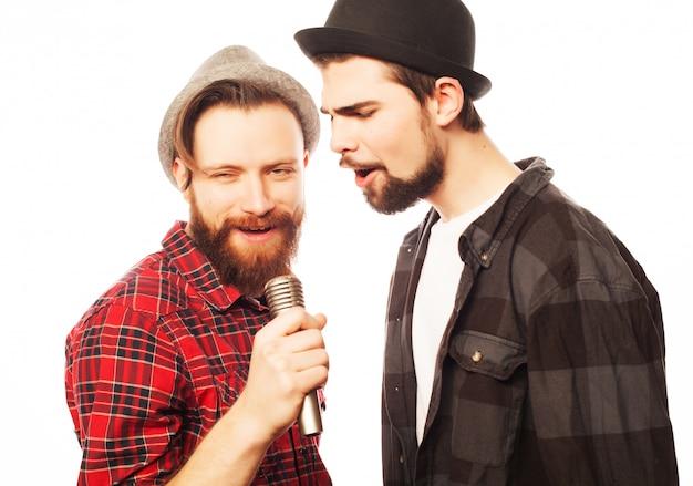 Hombres jóvenes cantando con micrófono