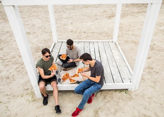 Hombres jóvenes comiendo pizza en la playa