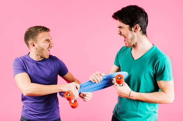 Hombres jóvenes compartiendo juguete longboard