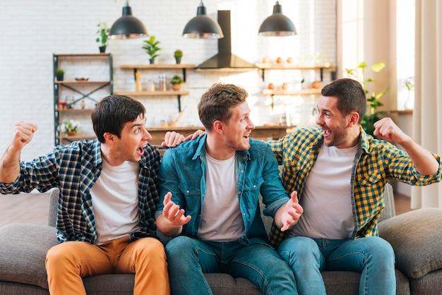 Hombres jovenes emocionados que se sientan en el sofá que anima en casa