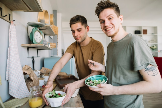 Hombres jovenes felices que comen jugo de la ensalada y de fruta en cocina