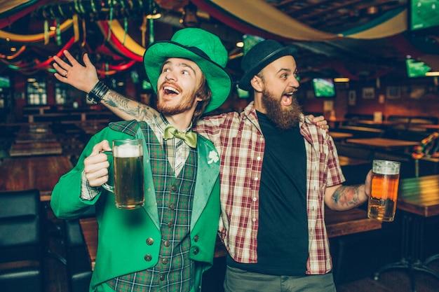 Hombres jovenes felices que sostienen las tazas de cerveza y que cantan juntas en pub. celebran el día de san patricio. el chico de la izquierda usa traje verde.